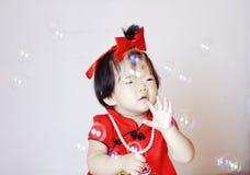 Piccolo bambino cinese divertente nelle bolle di sapone rosse del gioco del cheongsam Fotografia Stock