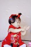Piccolo bambino cinese divertente nelle bolle di sapone rosse del gioco del cheongsam Immagini Stock