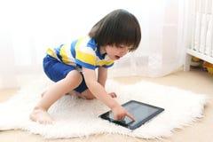 Piccolo bambino con il computer della compressa Fotografie Stock