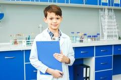 Piccolo bambino con l'apprendimento della classe nel fermacarte del laboratorio della scuola Immagini Stock