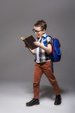 Piccolo bambino con la borsa di scuola che legge un libro Fotografie Stock
