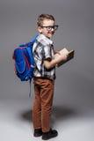 Piccolo bambino con la borsa di scuola e libro in studio Immagine Stock