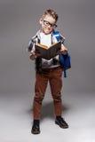 Piccolo bambino con la borsa di scuola e libro in studio Fotografie Stock