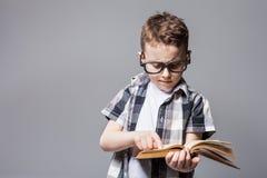 Piccolo bambino con la borsa di scuola e libro in studio Fotografia Stock