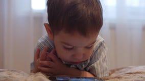 Piccolo bambino del CU, Little Boy che fa una pausa il telefono cellulare di sorveglianza del letto, infanzia felice video d archivio