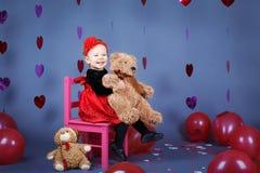 Piccolo bambino della neonata che si siede sulla piccola sedia rosa con il giocattolo dell'orso in studio Fotografia Stock