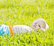 Piccolo bambino di sogno che pone sull'erba Fotografia Stock