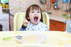 Piccolo bambino divertente che mangia il porridge del grano con la zucca Fotografia Stock Libera da Diritti