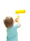 Piccolo bambino divertente con un grande rullo di vernice Immagine Stock