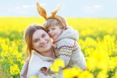 Piccolo bambino e sua la madre in orecchie del coniglietto di pasqua divertendosi, celebranti festa tradizionale di Pasqua Ragazz fotografia stock