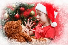 Piccolo bambino felice con i regali di Natale, orsacchiotto del giocattolo Natale con i regali e l'albero dei bambini Fotografia Stock Libera da Diritti