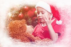 Piccolo bambino felice con i regali di Natale, orsacchiotto del giocattolo Natale con i regali e l'albero dei bambini Fotografia Stock