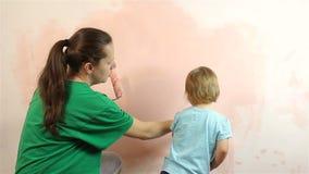 Piccolo bambino felice con la parete della pittura della mamma video d archivio