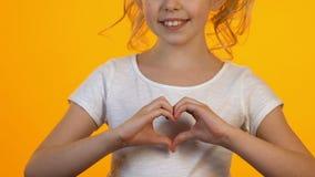 Piccolo bambino femminile che mostra il segno del cuore con le mani, sorridenti sulla macchina fotografica, concetto di amore archivi video