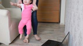 Piccolo bambino gioca con la mamma in scuola materna Bambino felice con il genitore che salta e che sorride in mani della mamma archivi video