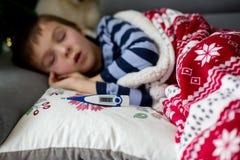 Piccolo bambino malato, ragazzo, con febbre alta addormentato sullo strato a Immagine Stock