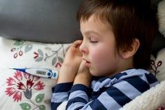 Piccolo bambino malato, ragazzo, con febbre alta addormentato sullo strato a Immagini Stock Libere da Diritti