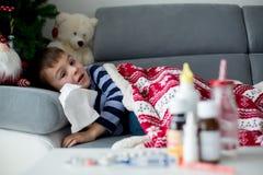 Piccolo bambino malato, ragazzo, con febbre alta addormentato sullo strato a Fotografia Stock