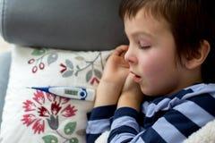 Piccolo bambino malato, ragazzo, con febbre alta addormentato sullo strato a Immagini Stock