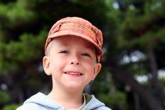 Piccolo bambino sorridente in protezione arancione Immagine Stock