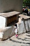 Piccolo bambino sulla punta dei piedi per raggiungere le ruote di preghiera Fotografie Stock Libere da Diritti