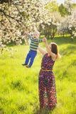 Piccolo bambino sulle mani della madre donna che gioca con il bambino fuori fotografia stock