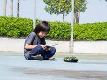 Piccolo bambino sveglio adorabile che gioca con il carro armato del giocattolo, immagini stock