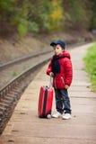 Piccolo bambino sveglio adorabile, ragazzo, aspettante su una stazione ferroviaria FO immagine stock libera da diritti