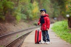 Piccolo bambino sveglio adorabile, ragazzo, aspettante su una stazione ferroviaria FO Fotografia Stock