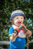 Piccolo bambino sveglio in cappello blu che tiene un giorno di estate soleggiato del tubo flessibile di giardino all'aperto Immagini Stock Libere da Diritti