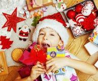 Piccolo bambino sveglio in cappello rosso con i regali fatti a mano, vint di Santa dei giocattoli Immagine Stock