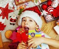 Piccolo bambino sveglio in cappello rosso con i regali fatti a mano, vint di Santa dei giocattoli Fotografia Stock Libera da Diritti
