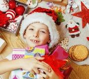 Piccolo bambino sveglio in cappello rosso di Santa con i regali fatti a mano, giocattoli inverno di legno e caldo d'annata Fotografia Stock