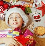 Piccolo bambino sveglio in cappello rosso di Santa con i regali fatti a mano, giocattoli inverno di legno e caldo d'annata Immagini Stock Libere da Diritti