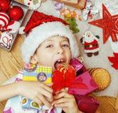 Piccolo bambino sveglio in cappello rosso di Santa con i regali fatti a mano, giocattoli inverno di legno e caldo d'annata Immagine Stock