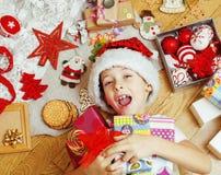 Piccolo bambino sveglio in cappello rosso di Santa con i regali fatti a mano, giocattoli inverno di legno e caldo d'annata, conce Immagine Stock Libera da Diritti