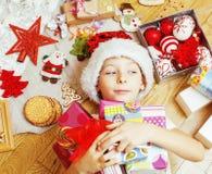 Piccolo bambino sveglio in cappello rosso di Santa con i regali fatti a mano, giocattoli inverno di legno e caldo d'annata, conce Immagine Stock