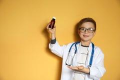 Piccolo bambino sveglio in cappotto di medico con il farmaco sul fondo di colore fotografie stock