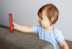 Piccolo bambino sveglio che prende lo smartphone della tenuta del selfie in sua mano, fotografia stock