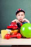 Piccolo bambino sveglio che si siede alla tavola in un'aula con gli accessori variopinti della scuola Immagine Stock Libera da Diritti