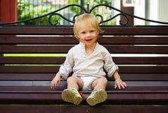 Piccolo bambino sveglio che si siede sul banco Fotografia Stock