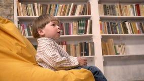 Piccolo bambino sveglio che si siede sulla sedia e sulla palla di cattura da qualcuno, fondo degli scaffali per libri stock footage