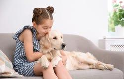 Piccolo bambino sveglio con il suo animale domestico sul sofà fotografia stock