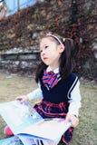 Piccolo bambino sveglio della ragazza che legge un libro sull'erba Immagini Stock
