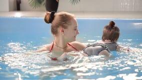 Piccolo bambino sveglio e sua la madre che hanno lezione di nuoto nello stagno La madre sta tenendo suo figlio in sue mani e video d archivio