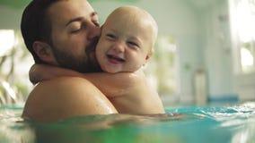 Piccolo bambino sveglio e suo il padre che hanno lezione di nuoto nello stagno Il padre sta tenendo suo figlio in sue mani e archivi video