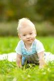 Piccolo bambino sveglio nel parco sull'erba. Bambino dolce all'aperto. Fotografie Stock