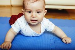 Piccolo bambino sveglio sulla fine del tappeto su che sorride, K adorabile del bambino fotografie stock