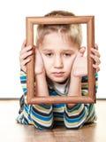 Piccolo bambino triste del ragazzo che incornicia il suo fronte Immagini Stock