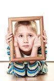 Piccolo bambino triste del ragazzo che incornicia il suo fronte Fotografia Stock